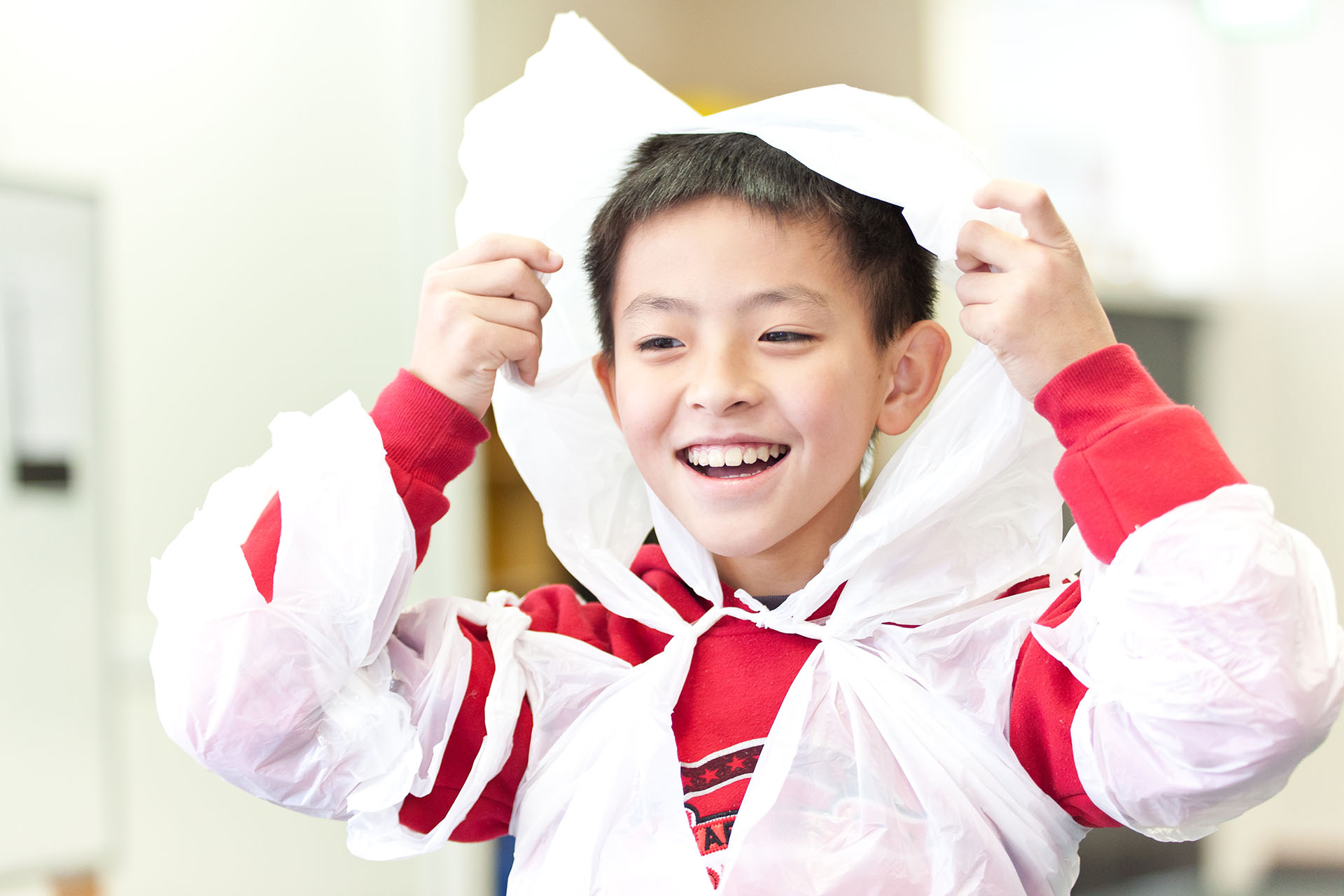 Smiling boy in protective cape in a painting class