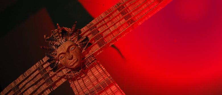 A Māori kite lit in red