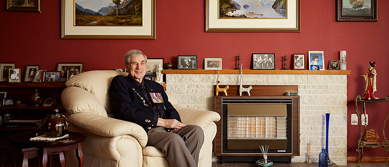 A veteran sits in his living room surrounded by photographs
