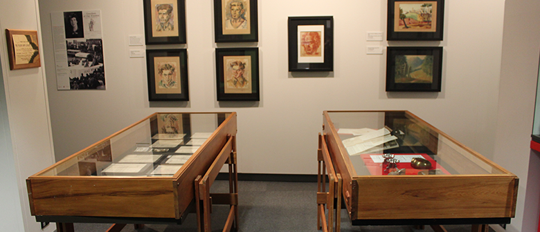 Drawings and objects created by Polish soldiers hang on the wall and are displayed in cases