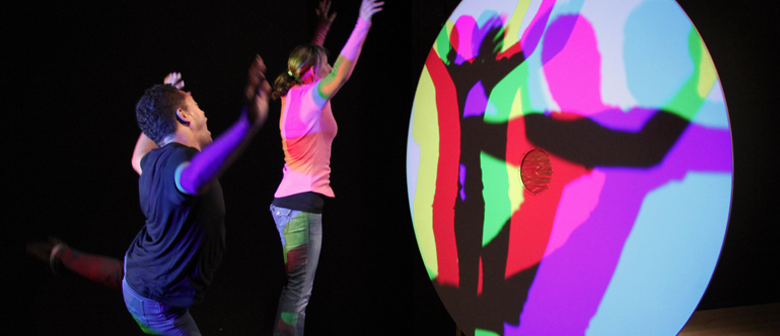 Two people dance in front of a light splitter, casting multi-coloured shadows on the wall