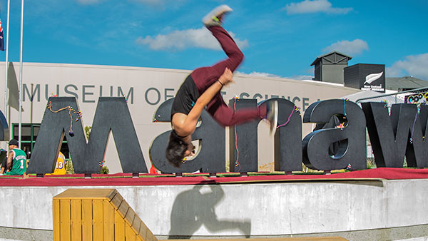 Young man does an acrobatic flip in front of the museum building