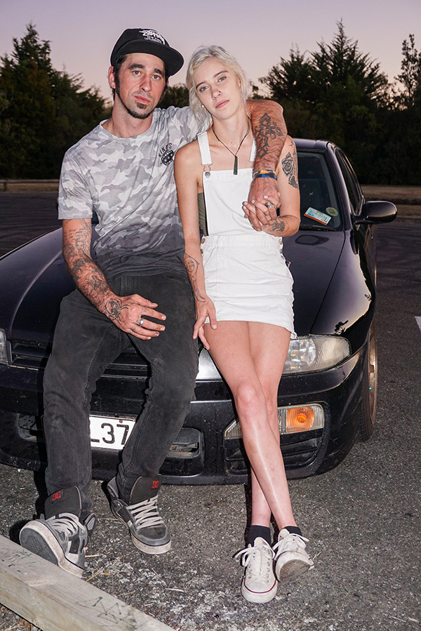Young couple pose leaning on a car