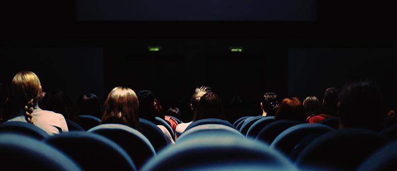 Children watch a movie in a dark theatre