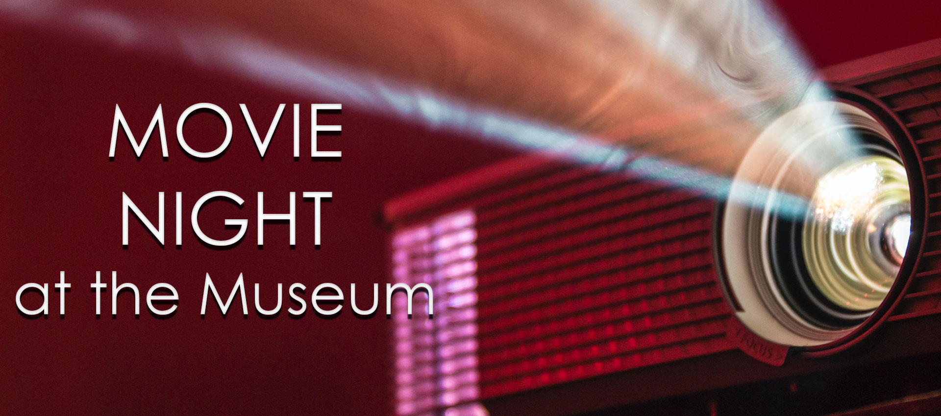 Text: Movie Night at the Museum, with light from a projector
