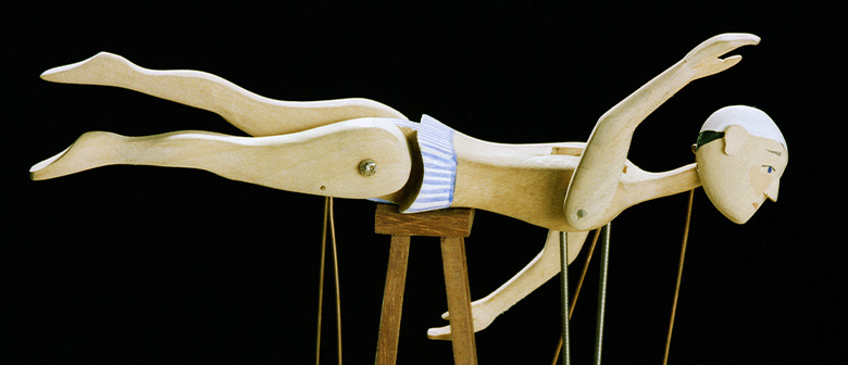 A wooden automaton of a swimming figure