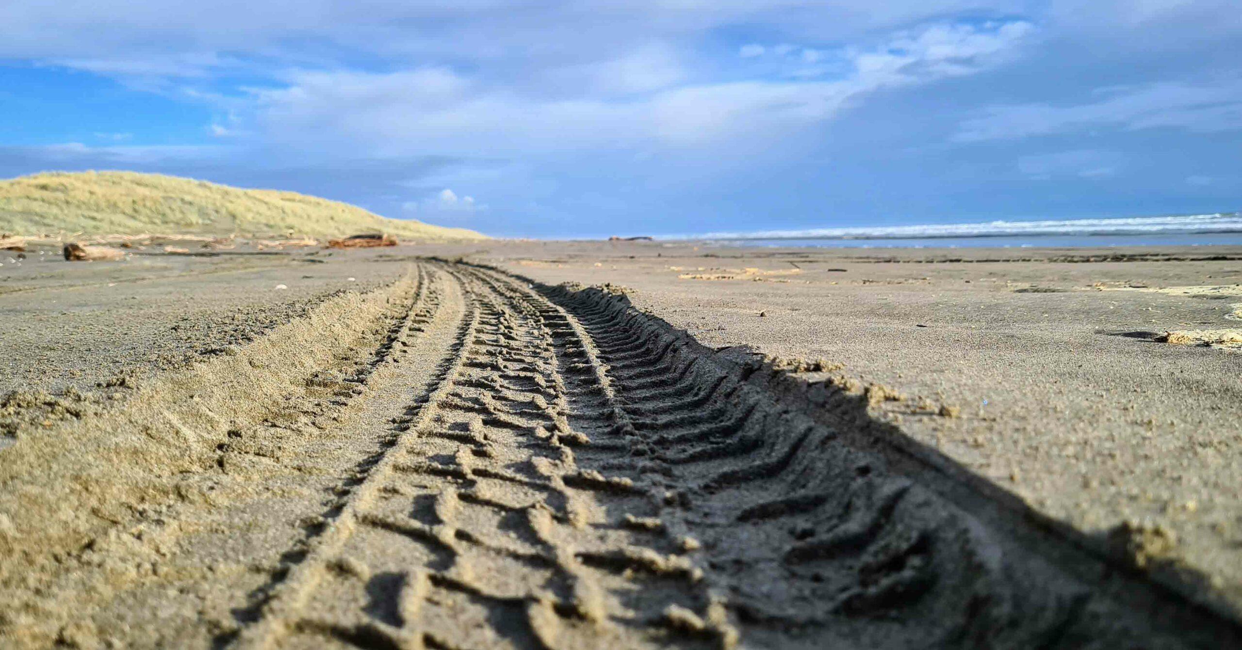 A tyre track across a beach
