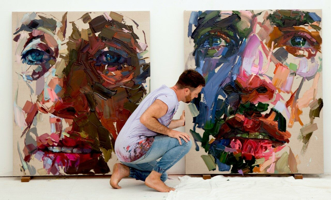 A man in front of two paintings of faces